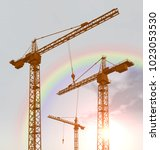 construction cranes and rainbow ... | Shutterstock . vector #1023053530