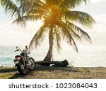 motorcycle near palm trees  sea ... | Shutterstock . vector #1023084043