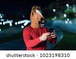 young horse man sending sms... | Shutterstock . vector #1023198310