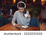 young woman listening to music...   Shutterstock . vector #1023231010