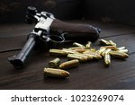 Small photo of Historic Luger P08 Parabellum handgun and shiny 9 mm bullets on wooden vintage background