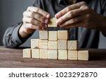 businessman building a pyramid... | Shutterstock . vector #1023292870