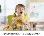happy little toddler girl plays ... | Shutterstock . vector #1023292954