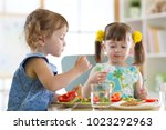 children eating food in daycare ... | Shutterstock . vector #1023292963