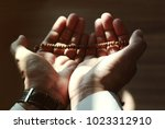 Small photo of Hands of Muslim Man Making Traditional Prayer To God with rosary while sunset.Light shining through the window and touched his hand.Backdrop light. Peaceful and Marvelous warm climate.Selective focus.