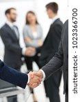 two businessmen shaking hands... | Shutterstock . vector #1023366700