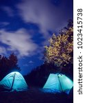 glowing tent in the mountains... | Shutterstock . vector #1023415738