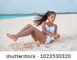 Small photo of Abs workout - fitness woman working out on beach doing russian twists abs exercises with raised legs for stomach weight loss toning. Fit body oblique muscles training Asian girl.