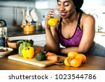 black woman is drinking orange... | Shutterstock . vector #1023544786