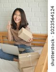 Small photo of happy laughing joyful accepting woman giving thumg up gesture with computer and product parcel box at home, successful work at home merchandise delivery concept