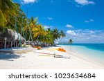 Small photo of Rangali, Maldives island - 14 July 2017: Beautiful sandy beach in the shade of palms for water sport with sail caramarans, boards and power boats, Maldives, 14 July 2017
