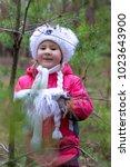 a cute little girl in a pine... | Shutterstock . vector #1023643900