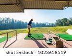 young woman practices her golf... | Shutterstock . vector #1023658519