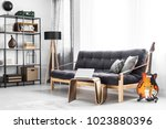 Electric guitar standing next to the window and wooden sofa with black futon in modern living room interior