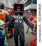 "Small photo of Cologne, Germany - February 12th 2018: Man dressed up as ""Fake News"" with an old TV set on his head during carnical celebrations in Cologne"