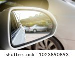 The car in the parking lot looking towards the side after the mirror looked. - stock photo