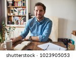 smiling young man sitting at a...   Shutterstock . vector #1023905053