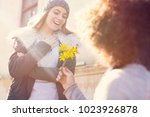 young man giving flower to his... | Shutterstock . vector #1023926878