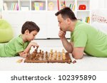 Playing chess with dad - young boy and his father at home - stock photo