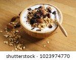 bowl of oat granola with yogurt ... | Shutterstock . vector #1023974770