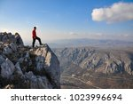 young man on a cliff edge on... | Shutterstock . vector #1023996694