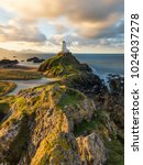 Small photo of Golden morning light on rocks at Llanddwyn Lighthouse on the Anglesey Coast, Wales, UK.