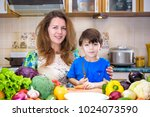 the young cook mother standing... | Shutterstock . vector #1024073590