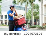 delivery man wearing helment to ... | Shutterstock . vector #1024073806