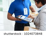 postman giving tablet computer... | Shutterstock . vector #1024073848