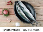 Stock photo two fresh mackerels in a black ceramic bowl with condiments upper plane 1024114006