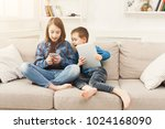 two kids with gadgets. sister... | Shutterstock . vector #1024168090