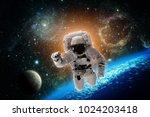 astronaut flies over the earth... | Shutterstock . vector #1024203418