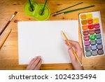 kids hand holding a pencil on... | Shutterstock . vector #1024235494