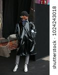 Small photo of MILAN - JANUARY 15: Man with shiny black coat and silver shoes before Pal Zileri fashion show, Milan Fashion Week street style on January 15, 2018 in Milan.