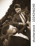 Small photo of Sure you need this? Vertical monochrome sepia shot of a handsome bearded barber cutting tie to his client standing on the edge of a canyon