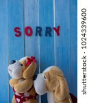 Small photo of Funny cute couple of soft toys dogs, begging for forgiveness with love from angry girlfriend with armcrossed and turn away from pity boyfriend. Color wooden letter word 'SORRY' on light blue wood wall