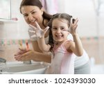 child girl and mother washing... | Shutterstock . vector #1024393030