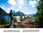 woman hiker takes a pictures of ... | Shutterstock . vector #1024453999
