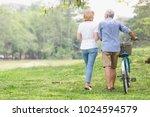 senior couple walking their... | Shutterstock . vector #1024594579