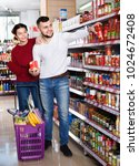 Small photo of Young cheerful couple standing near shelves with canned goods at store