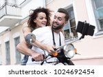 happy couple on scooter making... | Shutterstock . vector #1024692454