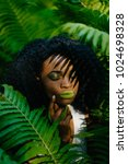 Small photo of Young alluring african girl with green eyeshadows and lipstick is softly touching her face in the fern garden. Green composition.