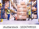 warehouse workers pulling a... | Shutterstock . vector #1024749010