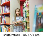 girl with books between shelves ... | Shutterstock . vector #1024771126