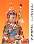 Small photo of The clay figurine of Padmasambhava - Guru Rinpoche, closeup,  colorful painted, isolated on an orange background.
