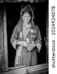 Small photo of PHONGSALY, LAOS - AUGUST, 2017 : Woman from the Akha tribe with traditional headgear standing outside house in mountains in the north of Laos .