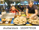 Small photo of Abstract blur image of merchants are selling food in the flea market with bokeh for background usage. (vintage tone)
