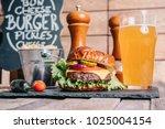 cheeseburger on a pretzel bun... | Shutterstock . vector #1025004154