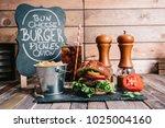 cheeseburger on a pretzel bun... | Shutterstock . vector #1025004160