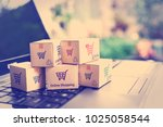 Small photo of Online shopping / ecommerce and delivery service concept : Paper cartons with a shopping cart or trolley logo on a laptop keyboard, depicts customers order things from retailer sites via the internet.